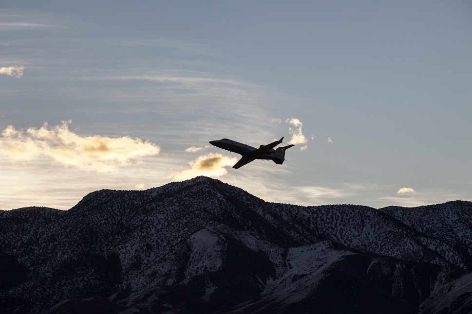 A Bombardier private Learjet takes off over mountains