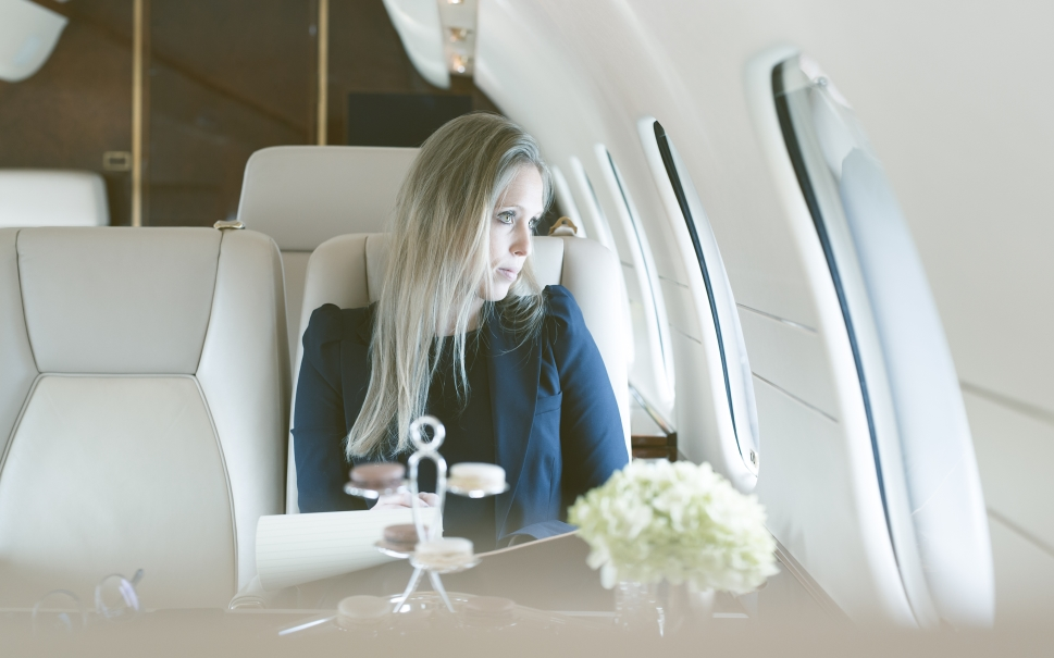 Mature blonde lady looks out of private jet window