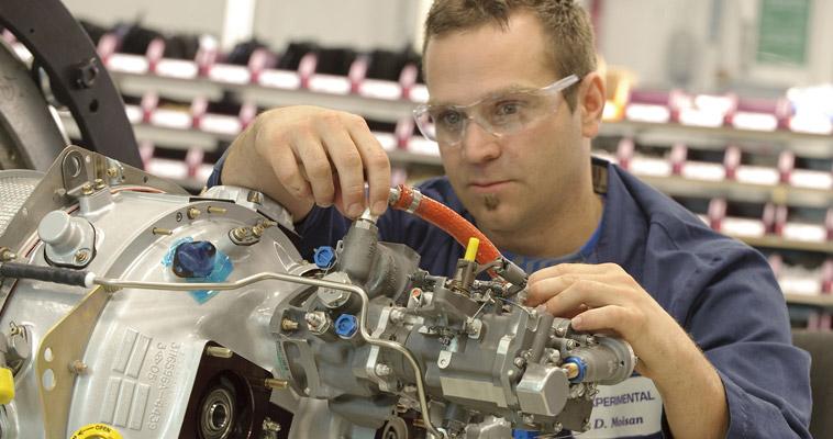 Mechanic maintains a Pratt & Whitney PT6A engine
