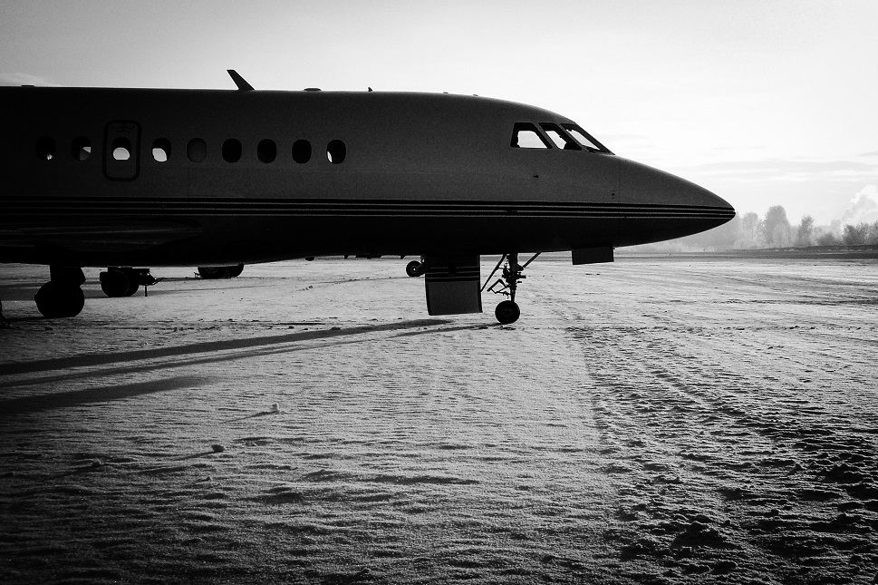 Dassault Falcon private jet parked on snow covered ramp