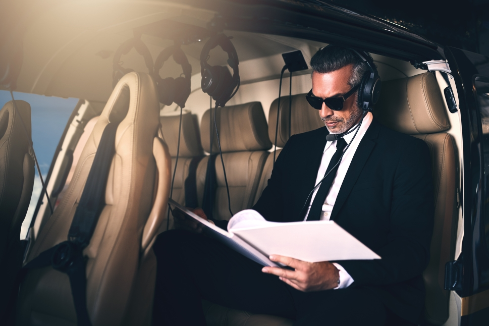 Executive aboard a private helicopter reading paperwork