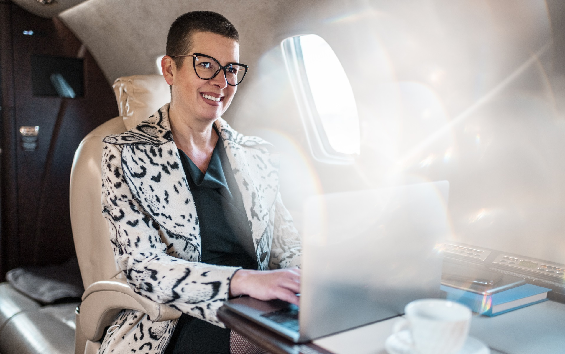 A busy executive uses her laptop aboard a Cessna Citation private jet