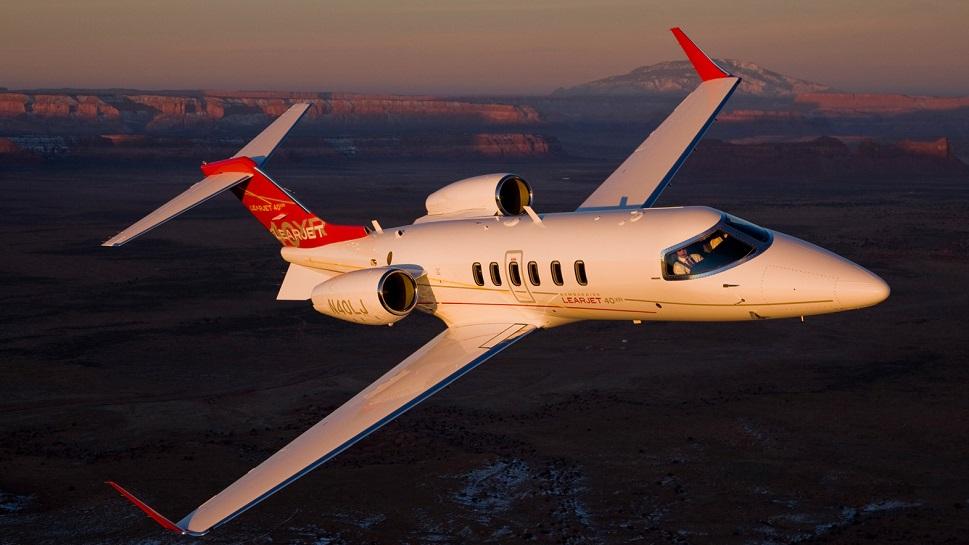 Bombardier Learjet 40XR in flight over mountainous terrain