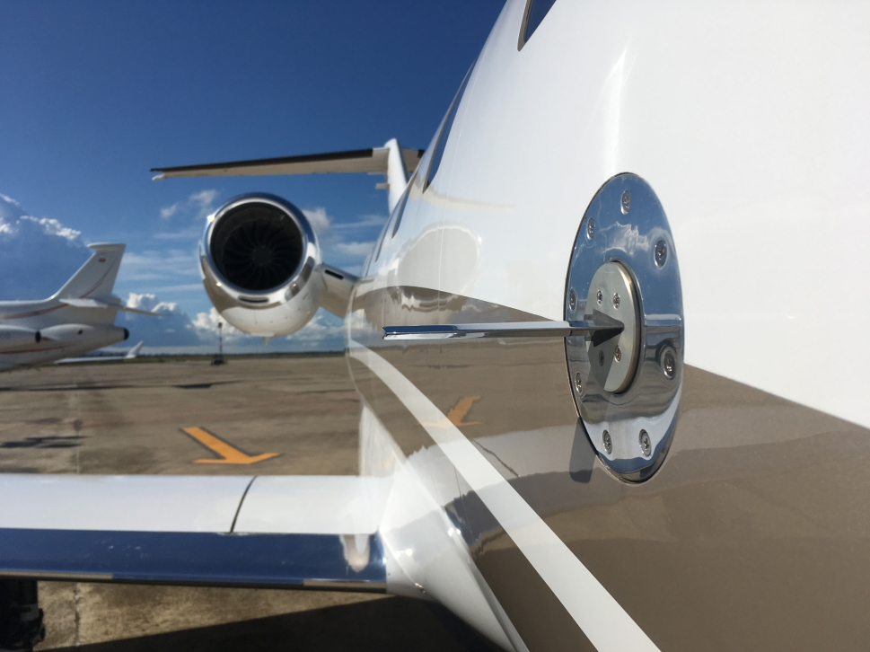 View along side of a small private jet and airport ramp in background