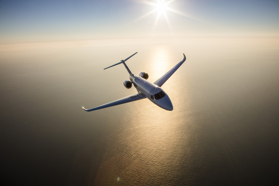 A Light Jet flies across a large body of water in clear blue skies