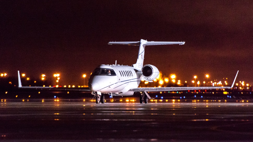 Bombardier Learjet on airport taxiway at night