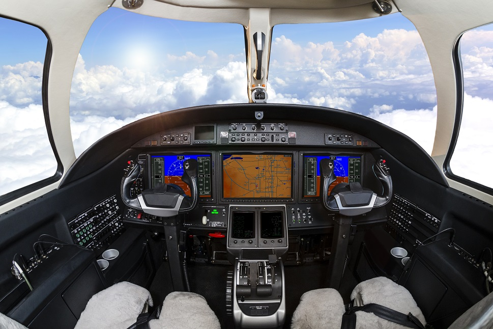 The empty cockpit of a small private airplane with flight panel lit up