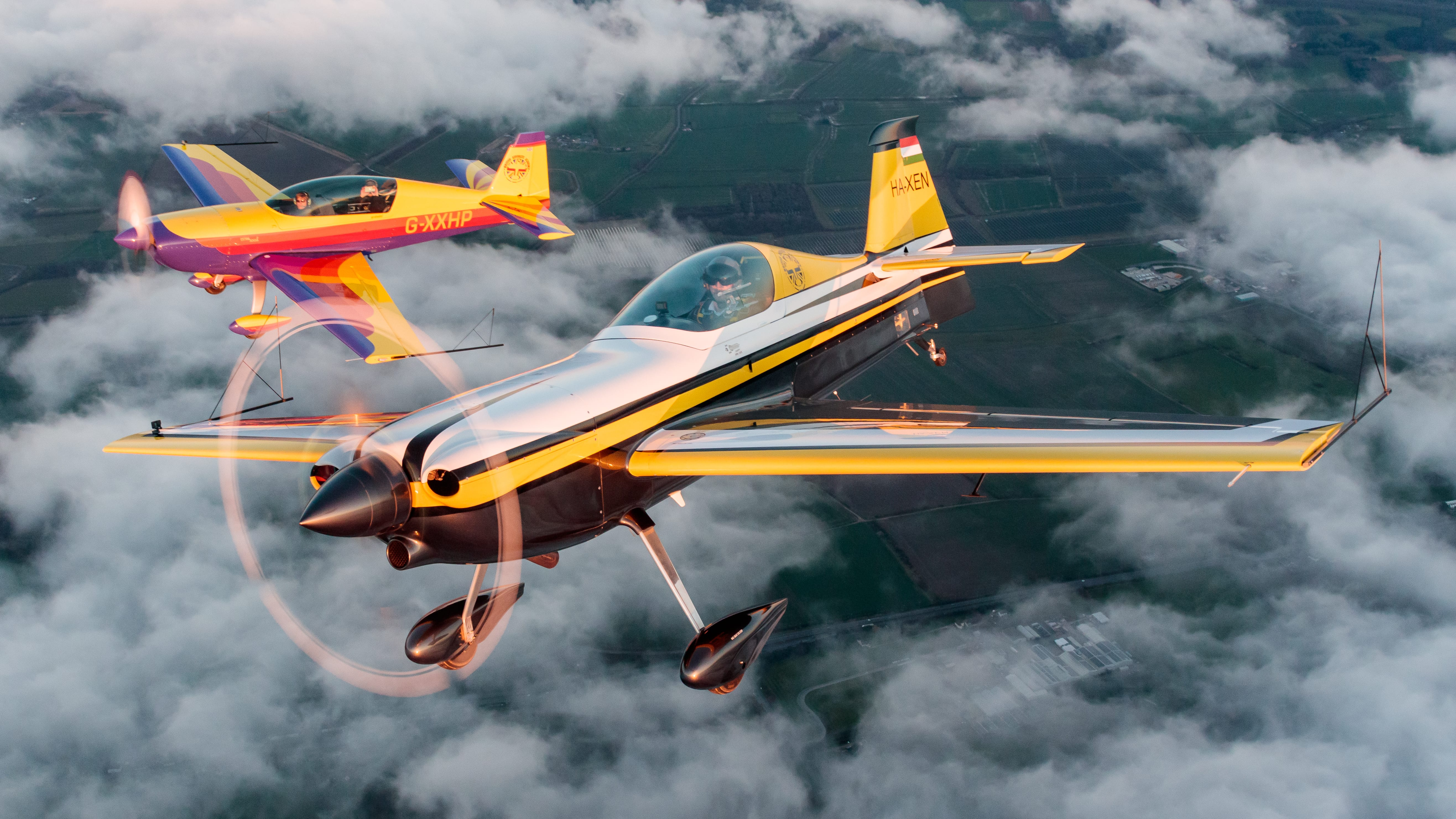 Two aerobatic aircraft flying through clouds