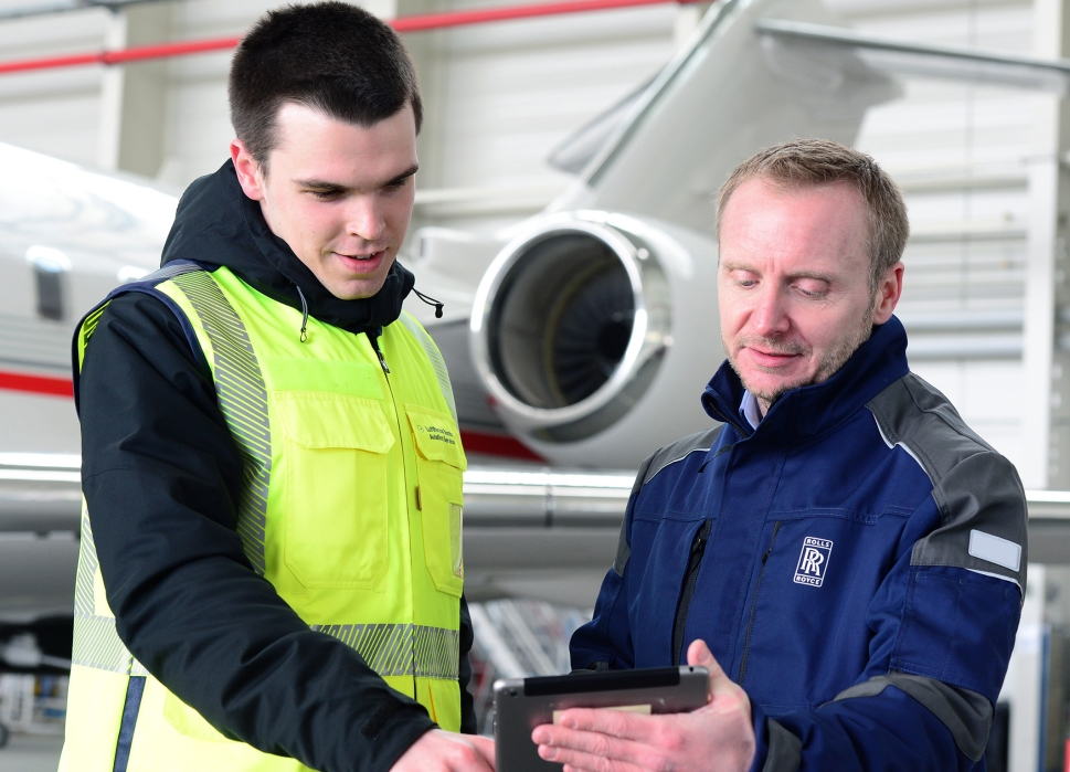 Rolls-Royce mechanics stand in front of a Bombardier private jet