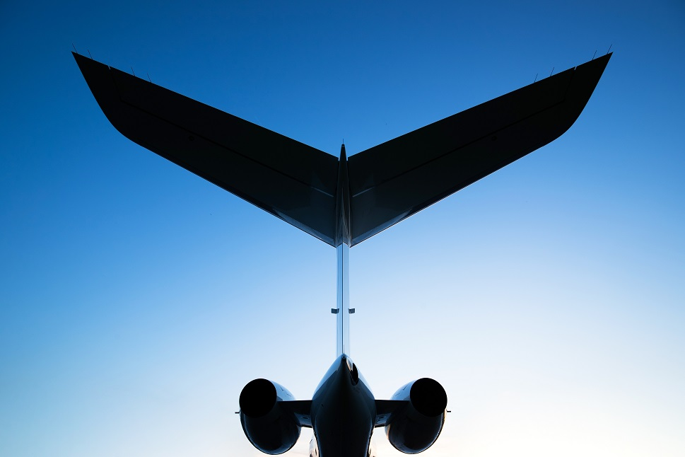 Private jet tail silhouette at sunset