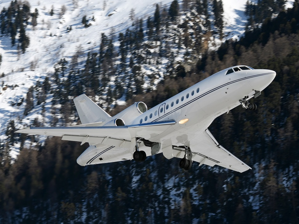 A Dassault Falcon private jet landing at a mountainous airport