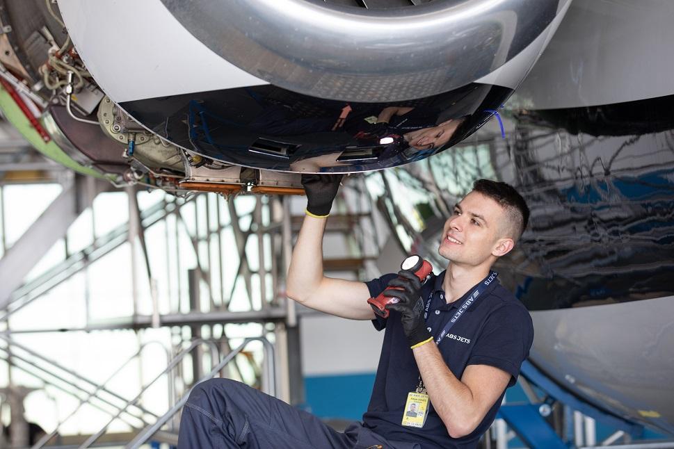 A maintenance technician examines a bizjet engine at ABS Jets