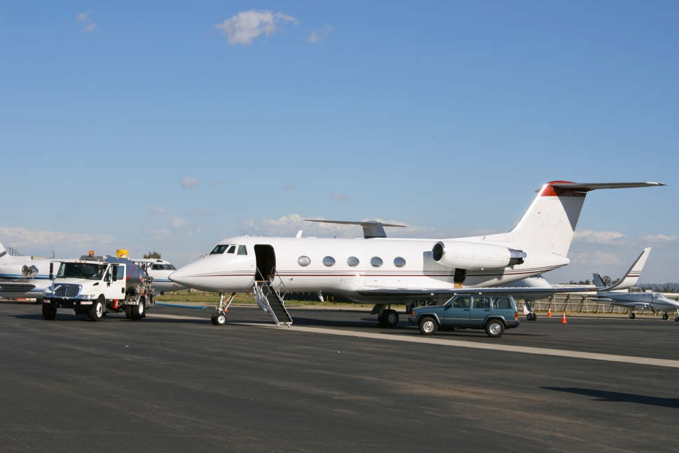 A Gulfstream private jet with a fuel truck parked next to it