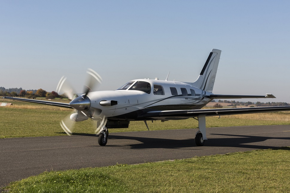 A Piper piston airplane taxis from the runway after landing