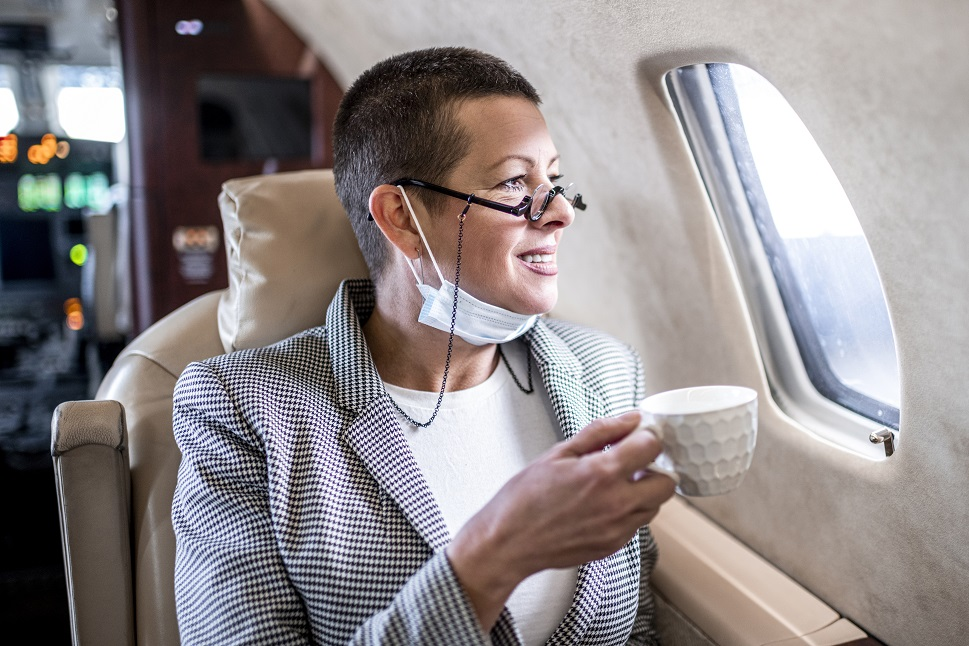 Smiling private jet passenger drinking coffee