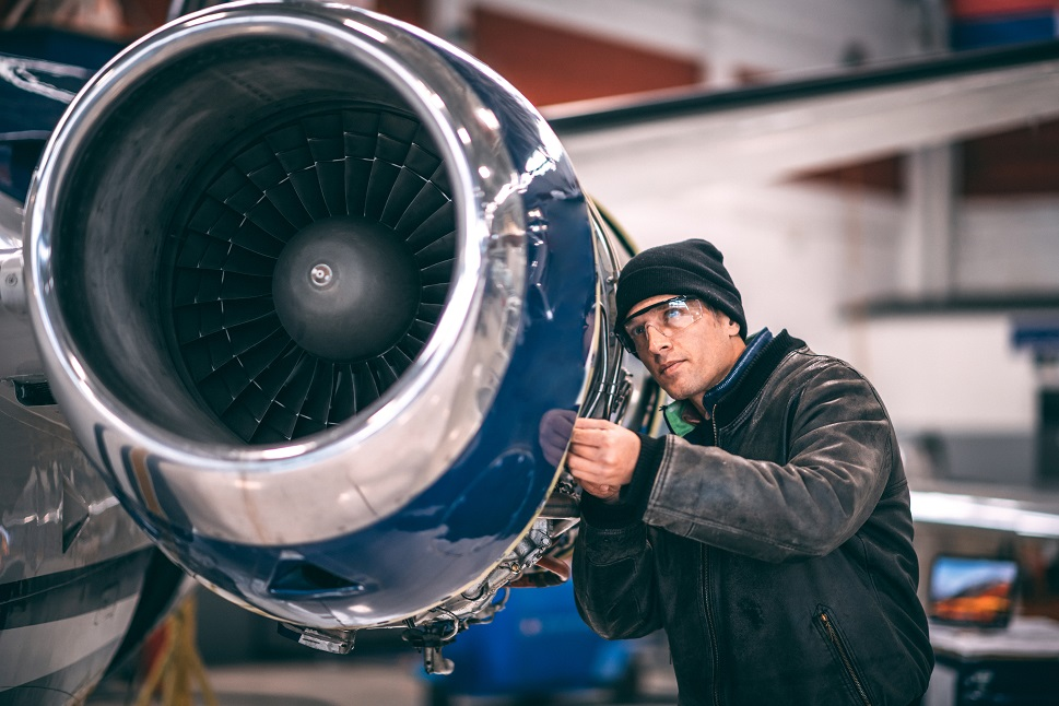 A business jet mechanic inspects the components of a powerplant