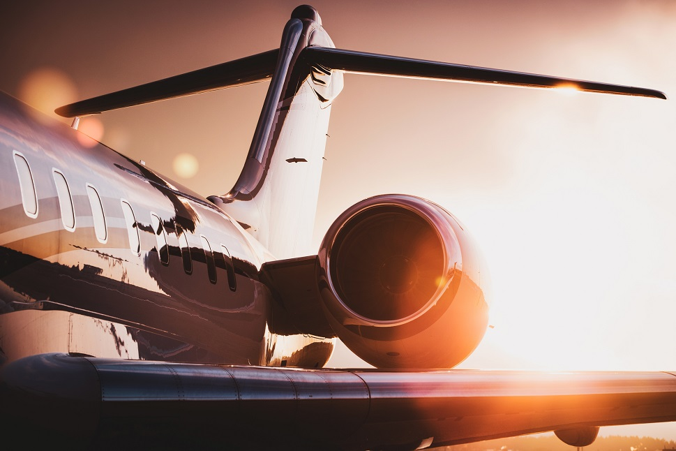 Sunlight reflects on the surface of a parked private jet