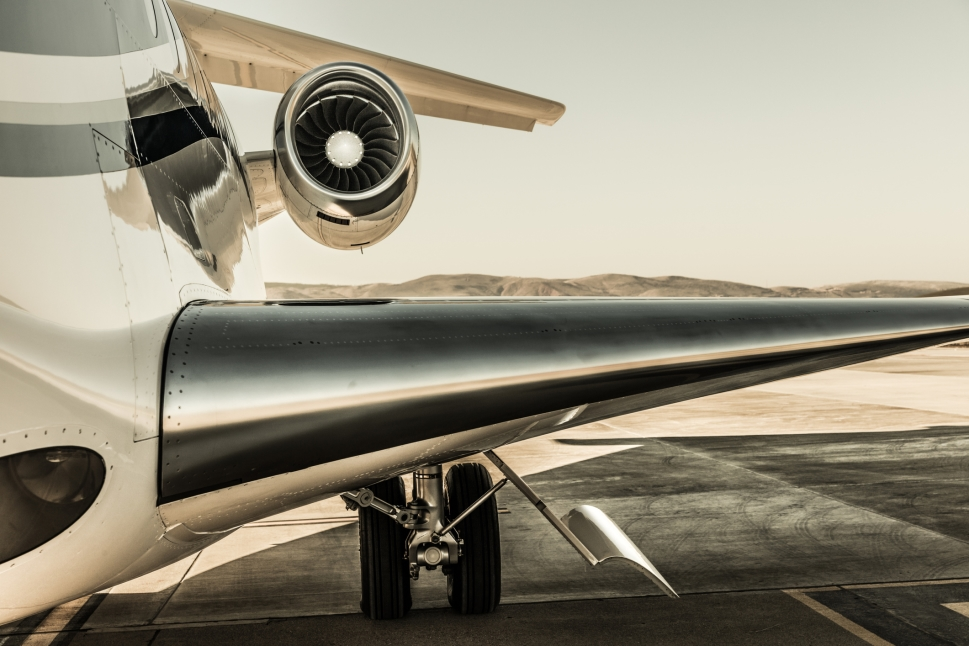 Overwing view of private jet engine and mountainous background