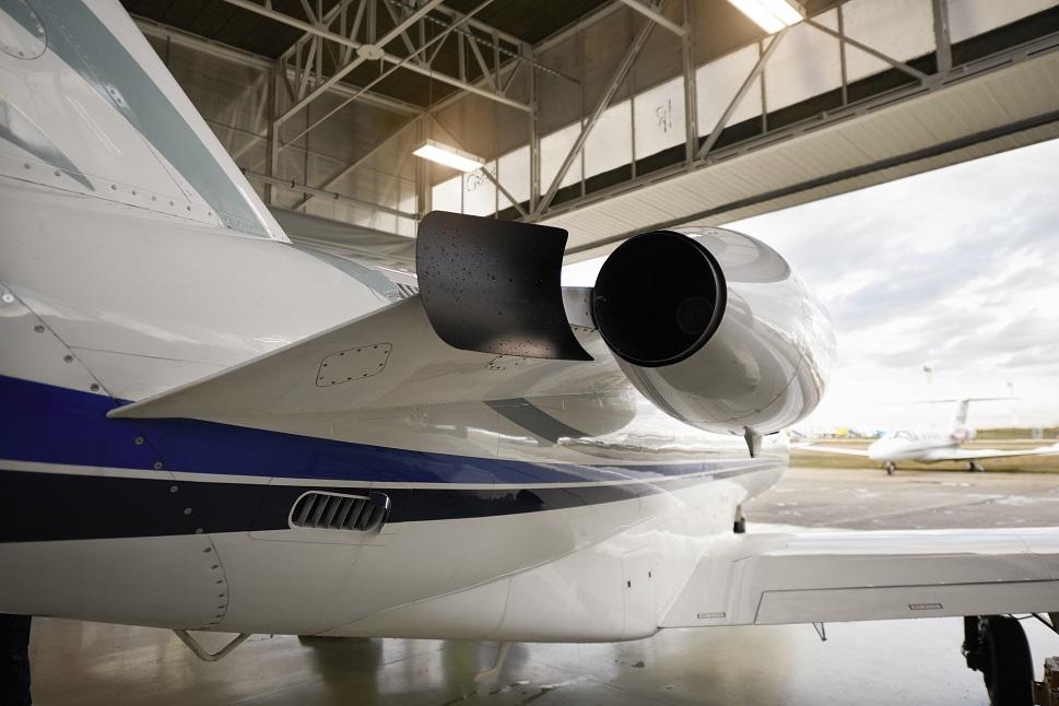 Cessna Citation private jet in hangar overlooking airport ramp