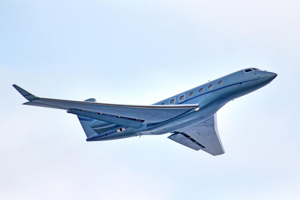 Gulfstream private jet flies through clear blue sky