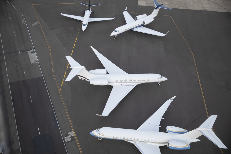 Different size private jets parked together on airport ramp