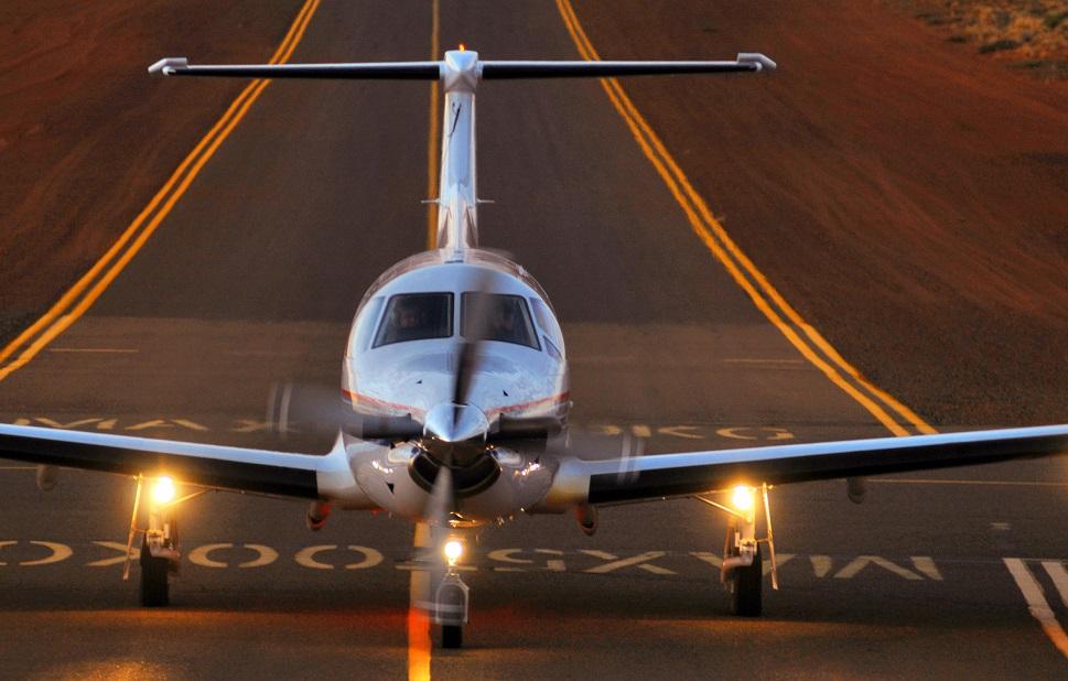 A Pilatus PC-12 turboprop aircraft landing on runway