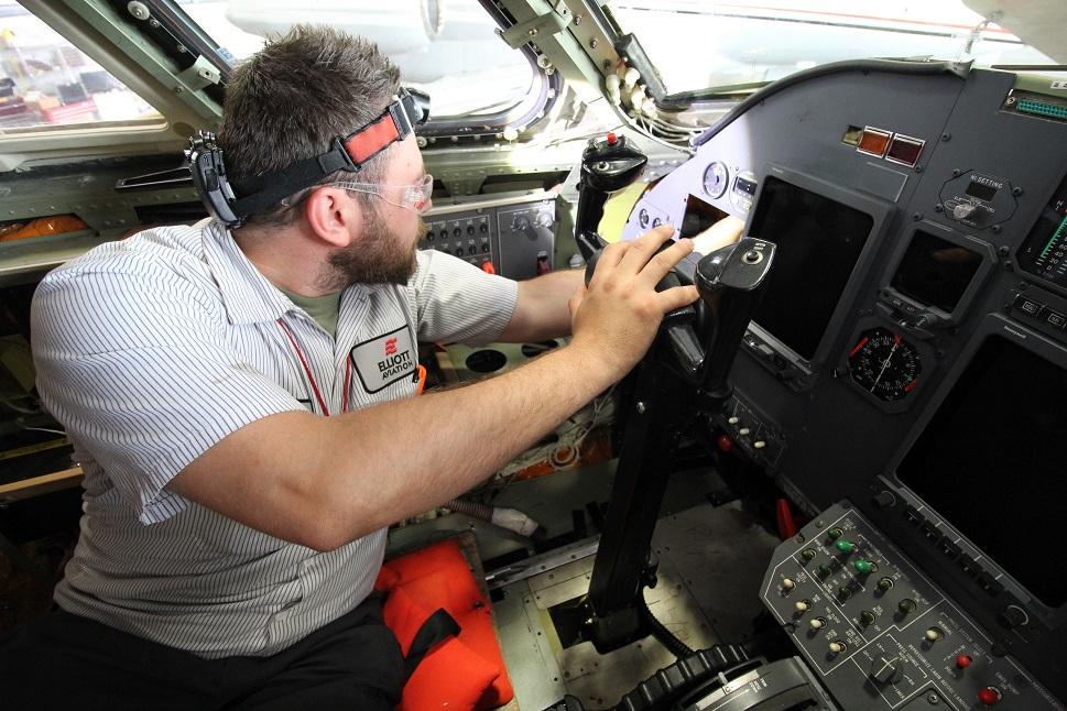 A mechanic at Elliott Aviation working of a flight panel retrofit
