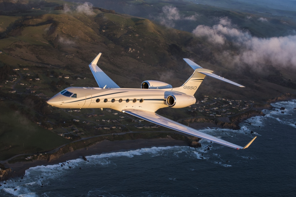 Gulfstream G550 private jet flies above coastal village