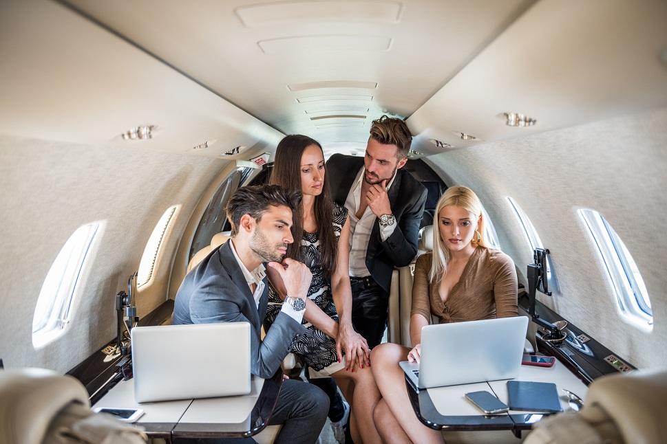 Private jet passengers discuss laptop presentation in flight