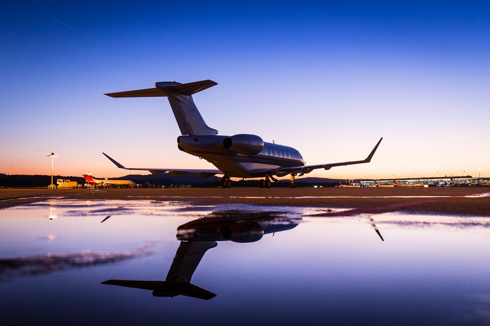 Bombardier Challenger private jet reflected in airport ramp puddles