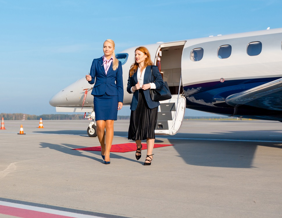 A business executive and stewardess exit a business jet