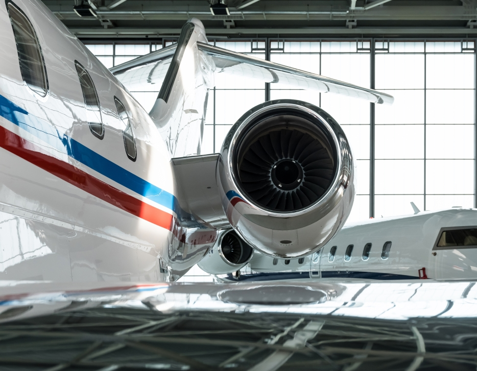 Overwings image of private jet engine and tail in aircraft hangar