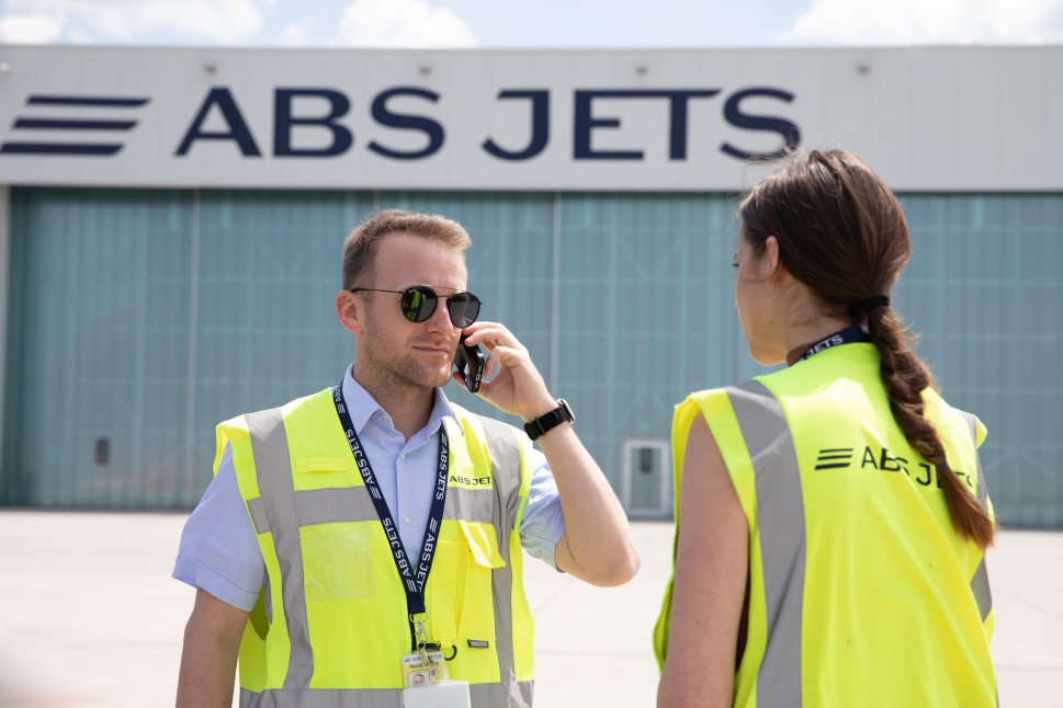Two ground support team members from ABS Jets stand outside hangar