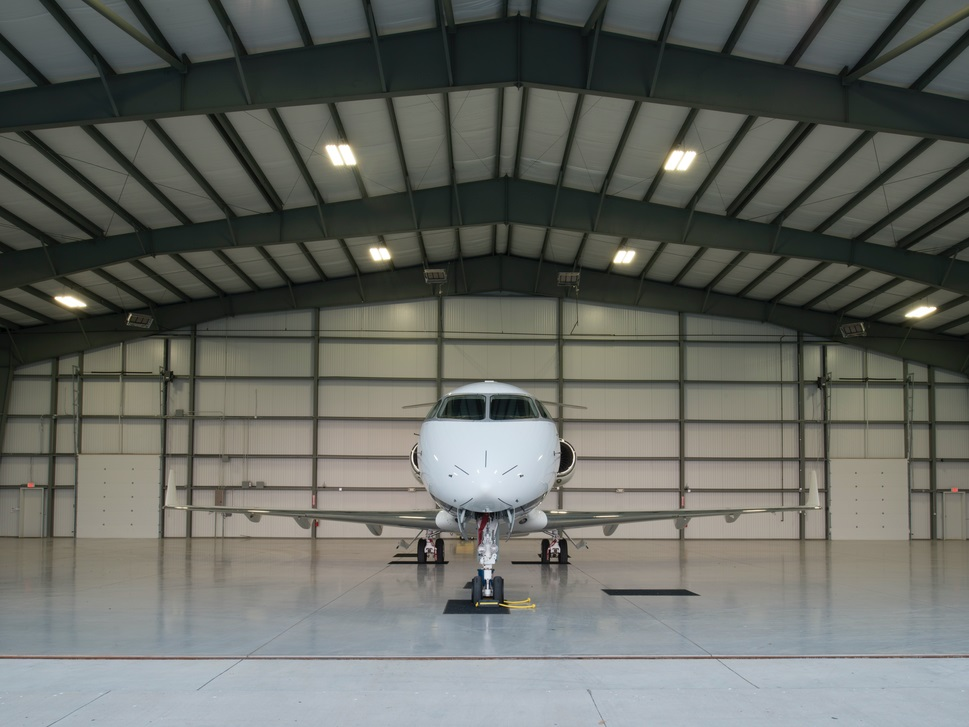 A private jet parked in an empty hangar