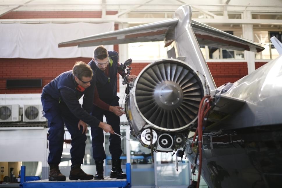 Aircraft mechanics inspect a private jet engine