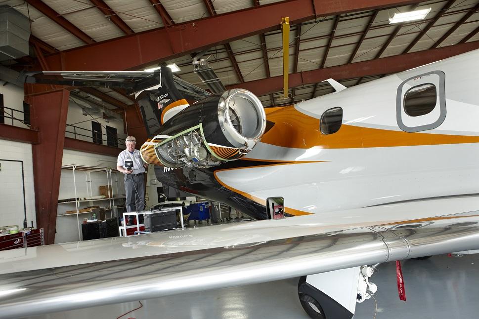 An MRO staffer at Elliott Aviation works on a Light Jet's powerplants