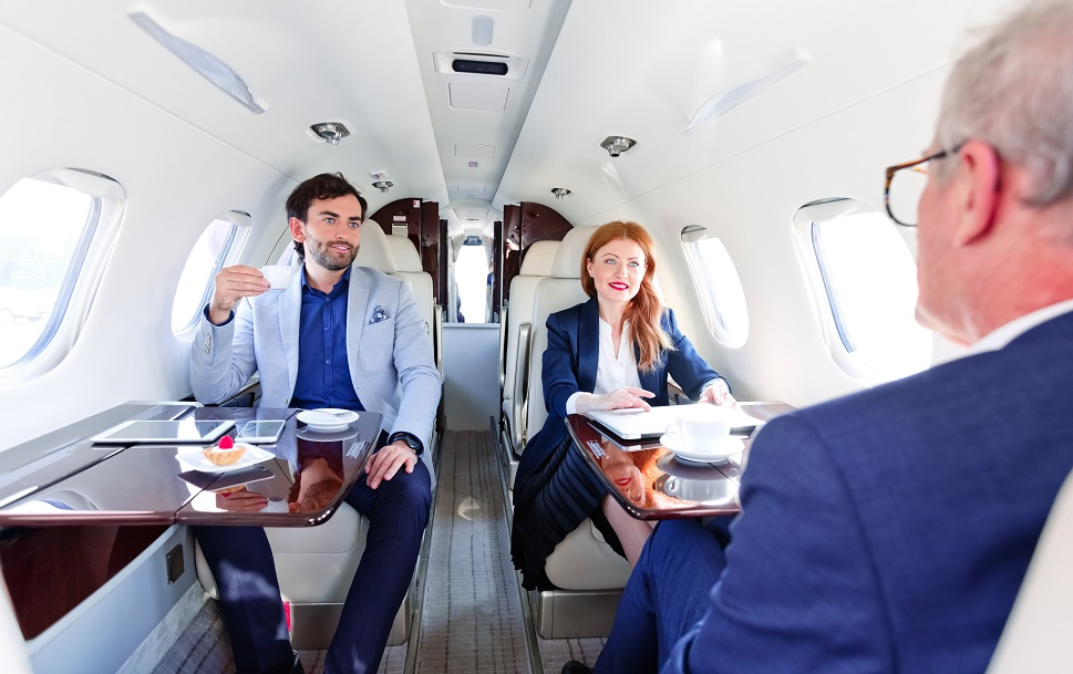 A corporate team hold a meeting in-flight aboard a private jet