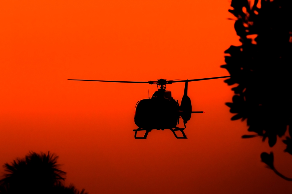 A private helicopter silhouetted against sunset sky