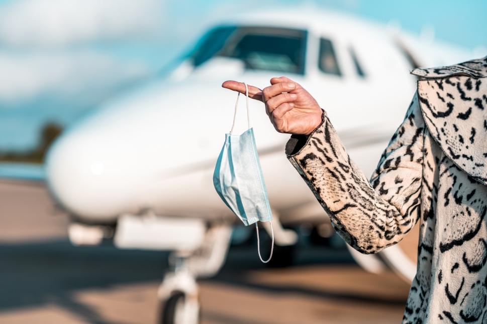 Female passenger holds Covid-19 face mask in front of Cessna Citation jet