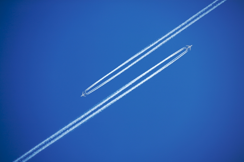 Aircraft pass each other at altitude, leaving contrails in their wake