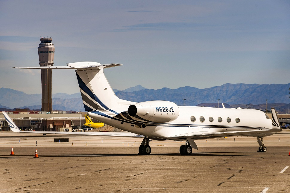 Gulfstream private jet with ATC tower in background