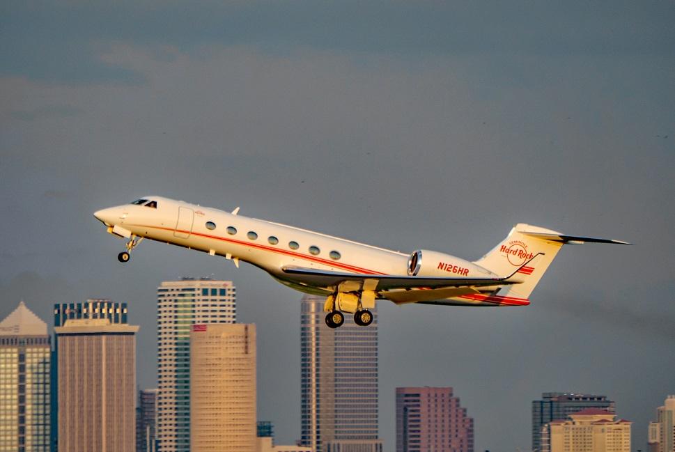Large Gulfstream private jet takes off - skyscraper backdrop