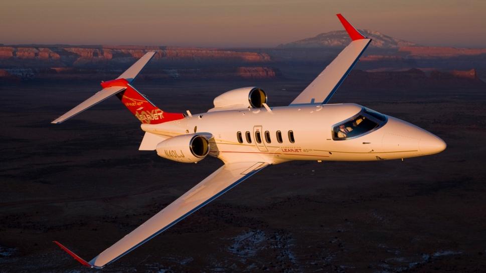 Bombardier Learjet 40XR private jet flies in early morning sun