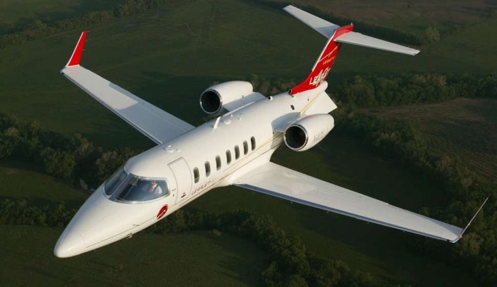Bombardier Learjet 40 private jet flies over fields