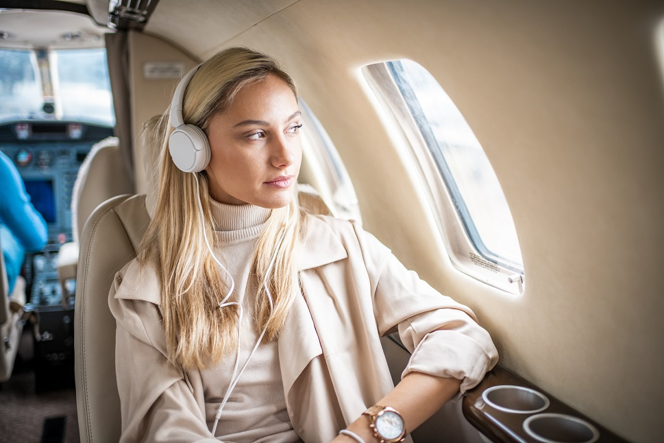 A private jet passenger relaxes to music aboard a private jet