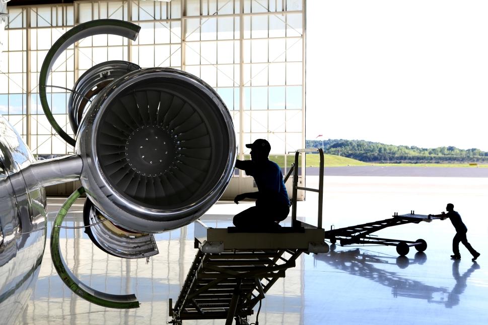Business jet engine mechanic works on aircraft powerplant