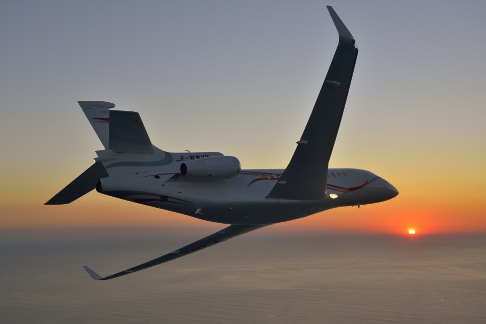 Dassault Falcon 7X private jet flies at sunset