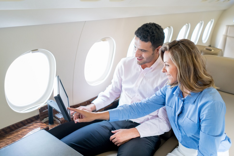 Business man and woman interact aboard a private jet
