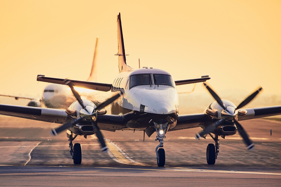 Beechcraft King Air twin engine turboprop with commercial airliner in the background