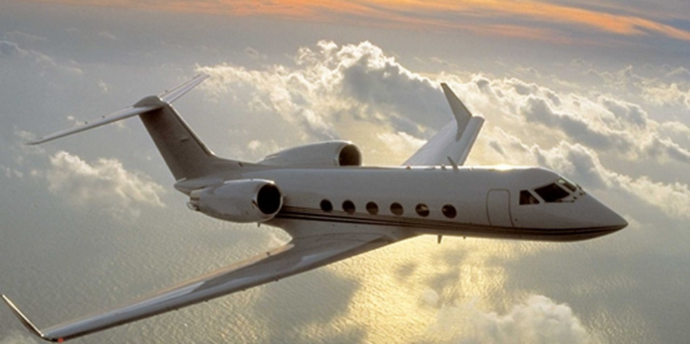 Gulfstream GIV flies over sunlit clouds at sunset
